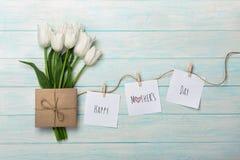 白色郁金香和信封花束与贴纸与晒衣夹在绳索和蓝色木板 日母亲s 库存照片