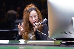 Μια γυναίκα-υποδοχή ορκίζεται με τον πελάτη τηλεφωνικώς στοκ εικόνες με δικαίωμα ελεύθερης χρήσης