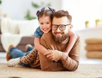 Ημέρα πατέρα Η ευτυχής οικογενειακή κόρη αγκαλιάζει τον μπαμπά του στοκ φωτογραφία
