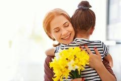 Ημέρα της ευτυχούς μητέρας! η κόρη παιδιών δίνει στη μητέρα μια ανθοδέσμη των λουλουδιών στους ναρκίσσους και το δώρο στοκ εικόνες