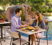 S-3232-Couple eating taquitos at poolside Stock Image