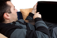 That's It. Young man showing something on his notebook display while laying in bed Stock Images