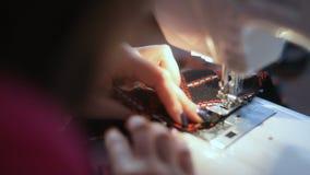 Κινηματογράφηση σε πρώτο πλάνο των χεριών γυναικών ` s που ράβουν μια αυτόματη συσκευή overlock το υλικό χόμπι επεξεργασίας έκοψε απόθεμα βίντεο