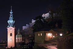 ` S Abbey Church de San Pedro y fortaleza de Hohensalzburg en la noche Salzburg, Austria Fotos de archivo