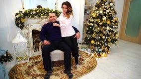S'aimant le mari et l'épouse sont heureux ensemble et posant pour l'appareil-photo, se reposant sur le fauteuil dans le salon clips vidéos