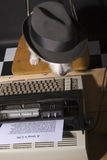 It's all about me. West Highland Terrier wearing a man's hat sitting on a chair in front of a typewriter stock photos