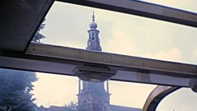 1970s Amsterdam monuments. Sea view of monuments and clock tower by boat tour in Amsterdam town of Holland. Historical archival touristic cruise in Amsterdam stock video