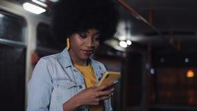 S atractivo, mujer afroamericana joven iling que usa smartphone en el transporte público Puente de la bah?a en San Francisco, CA  almacen de metraje de vídeo