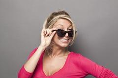 20s atrakcyjna dziewczyna patrzeje nad jej okularami przeciwsłonecznymi z uśmiechem Zdjęcia Royalty Free