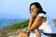 40s atrativos amadurecem a mulher com o livro que olha o horizonte pensativo Foto de Stock Royalty Free