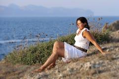 40s atrativos amadurecem a mulher que senta-se apenas na praia que pensa e que olha o horizonte pensativo Fotografia de Stock