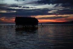 S'attaquer dans l'homme de hutte au coucher du soleil Photographie stock