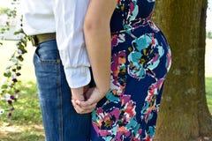 S'attendre à des couples de nouveau au dos tenant des mains photographie stock libre de droits