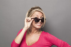 20s attractive girl looking over her sunglasses with a smile Royalty Free Stock Photos