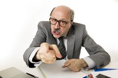 60s bald senior office boss man furious and angry gesturing upse. T and mad sitting on desk with paperwork in business and job problems and stress concept Royalty Free Stock Image