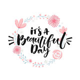 It's a beautiful day. Brush lettering in floral wreath. Inspirational quote, modern calligraphy Royalty Free Stock Images