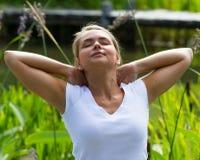 20s blond dziewczyna cieszy się relaksować w słońce upale w parku Obrazy Royalty Free