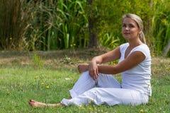 20s blond dziewczyna cieszy się spokój w zielonym miasto parku Zdjęcie Stock