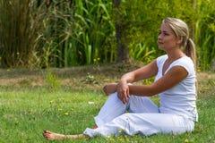 20s blond dziewczyna cieszy się spokój w zielonym miasto parku Fotografia Royalty Free