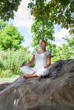 20s blond dziewczyna medytuje pod drzewem na skale Obrazy Stock