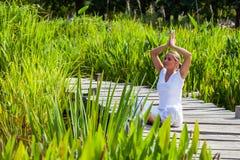 20s blond dziewczyna medytuje w zielonych surrondings Obraz Royalty Free