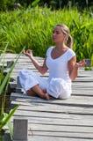 20s blond dziewczyna medytuje w zielonych surrondings Zdjęcie Stock