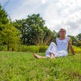 20s blond dziewczyna odpoczywa w zielonej trawie Zdjęcia Stock