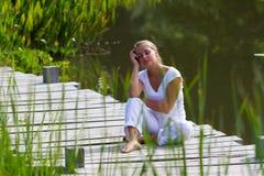 20s blond dziewczyna relaksuje i marzy blisko wody Zdjęcie Stock