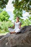 20s blond dziewczyna relaksuje pod drzewem na kamieniu Obrazy Stock