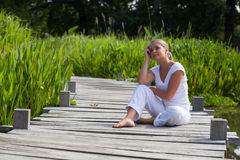 20s blond girl dreaming in the sun relaxing near water Royalty Free Stock Photography