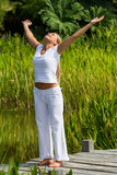 20s blond girl enjoying opening her arms wide near water Stock Photography