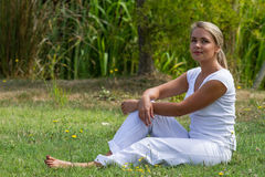 20s blond girl enjoying quietness in green city park. Relaxation outdoors - thinking young woman resting on grass with bare feet,green surrounding,summer Stock Photo