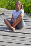 20s blond girl enjoying relaxing outdoors. Relaxation outside - beautiful young woman with bare feet relaxing in sitting on a wooden bridge in green environment Royalty Free Stock Photo