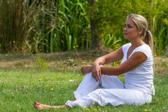 20s blond girl enjoying serenity in green city park. Relaxation outdoors - thinking young woman resting on grass with bare feet with green surrounding, profile Royalty Free Stock Photography