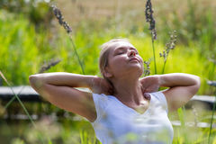 20s blond girl enjoying sun and free time near water. Relaxation outside - relaxed young woman daydreaming,enjoying sun and vacation with green surrounding Stock Image