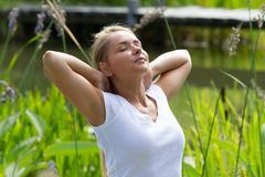 20s blond girl enjoying sun heat in green park. Relaxation outdoors - happy young woman breathing,enjoying sun and vacation with green surrounding, summer Royalty Free Stock Photography