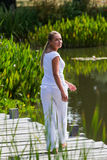 20s blond girl enjoying walking on pontoon near water. Relaxation outside - happy young woman walking on a wooden bridge, turning herself to the camera,exotic Royalty Free Stock Photography