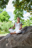20s blond girl meditating under a tree on a rock Stock Images