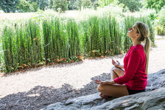 20s blond girl practicing yoga in a city park Royalty Free Stock Images