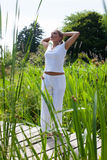 20s blond yoga girl outstretching near water Royalty Free Stock Photo