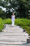 20s blond yoga girl walking near water. Relaxation outside - relaxed young woman with bare feet walking actively on a wooden bridge with water and green Royalty Free Stock Photos