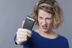 20s blonde girl disappointed about her image on smartphone Stock Photography
