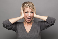 20's blonde girl in pain, suffering from migraine or avoiding noise Royalty Free Stock Image