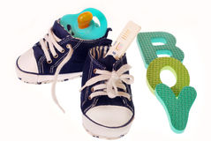 It`s a boy !. Baby boy`s shoes with pregnancy test  dummy and letters b,o,y, isolated on white Royalty Free Stock Images