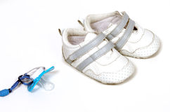 It's a boy! Blue baby's dummy and shoes Royalty Free Stock Images