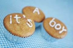 It's a boy cakes. Closeup of three cakes or buns with icing spelling words, It's a boy, blue background Royalty Free Stock Photos
