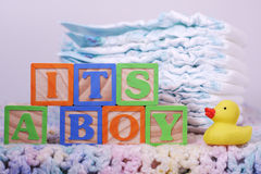 It's A Boy Crochet Blanket. It's a Boy spelled out in wooden letter blocks with yellow rubber duck and diapers Stock Photo