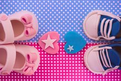 It`s a boy and a girl. Twins baby shower invitation. Is it a boy or a girl concept. Girl and boy baby shoes on blue and pink background. Twins baby shower. Baby stock photo
