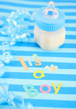 It's a  boy milk bottle. A blue baby bottle with milk and celebratory it's a boy text and  ribbon suitable for new baby Royalty Free Stock Photo