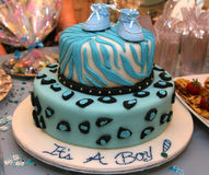 It's a boy shower cake. Two tier baby shower cake with marzipan icing and baby shoes as decoration Stock Photography